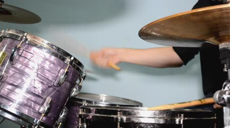 Drummer playing on drum set with puprple drum and cymbals, playing with sticks