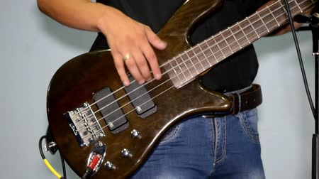 Guitarist plays on a brown bass in studio, dressed in jeans and a black shirt Stock mozgókép