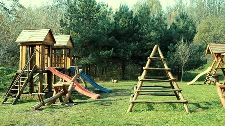 Childrens playground in summer with swings and slides, made of wooden beams Stock mozgókép
