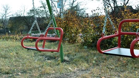 Childrens playground in summer with the red swing, which is empty and swinging Stock mozgókép