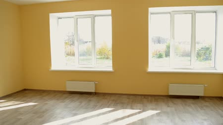 Large yellow empty room with large windows after repair and restoration