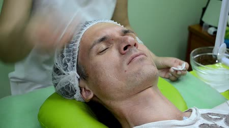 A beautician rubs man skin with cotton pad with cleansing agent before procedure