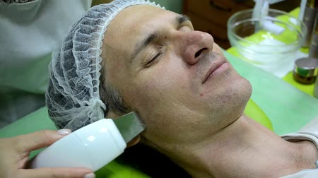 Beautician does cleaning on face of a white man with ultrasound device