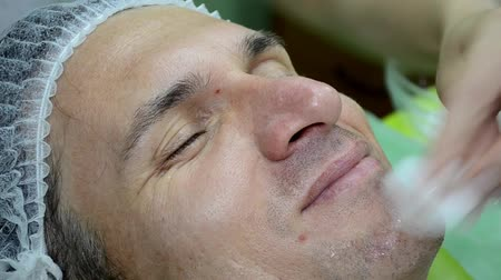 Beautician does procedure on the face of man with ultrasound device closeup