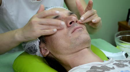 Beautician applies the cream on face of man, applies moisturizer around eyes Stock mozgókép