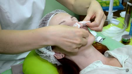 Beautician rubs the skin of a white woman with cotton pad with a cleansing agent Stock mozgókép