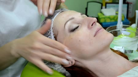 The beautician puts cream on face of white woman with hands, the woman smiles