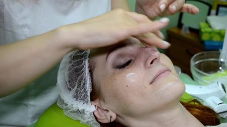 Beautician applies a moisturizer all over the face of white woman with hands