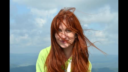 Slideshow with redhead girl in an orange jacket happy laughs on top of mountain