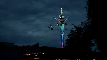 Attraction carousel on a long stock, multi-colored with light bulbs in dark time Stok Video