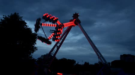 Extreme attraction in Lunapark, with different lights, filmed in dark in work Stock mozgókép