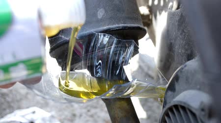 Pouring motor oil into motorcycle tank through piece of plastic bottle, lifehack