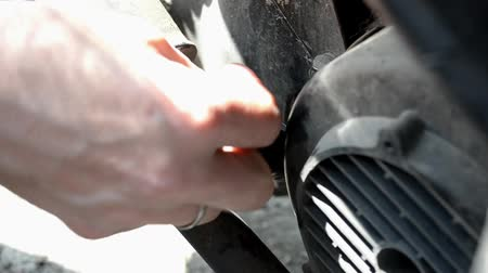 válvula : Checking the level of engine oil in a motorcycle, a man unscrews the valve