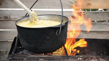 Wheat cereal with meat is prepared on grill, it is stirred with spoon, closeup Stok Video