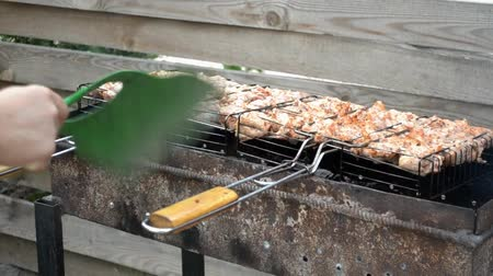 пожар : Chicken appetizing meat is fried on the grill, a man fanning the fire for the heat Стоковые видеозаписи