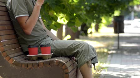 A man in green close sits on a wooden bench in the alley under a tree and drinks coffee from a red cup, his face is not visible