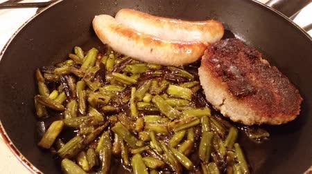 schabowy : Green beans, sausages and schnitzel fried in a pan Wideo