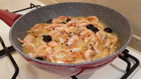 koření : Shrimps with heads, olives and garlic fried in oil in a pan on a gas stove