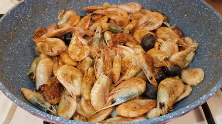 Shrimps with heads, olives and garlic fried in oil in a pan on a gas stove