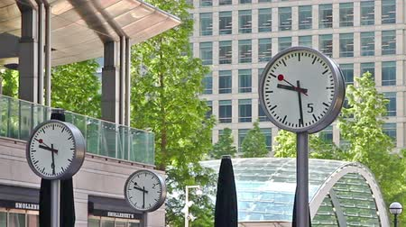 docklands : LONDON, UK - APRIL 30, 2015: Canary Wharf square with clocks. Time lapse Stock Footage