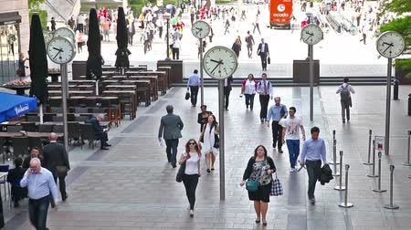 irodai dolgozó : LONDON, UK - APRIL 30, 2015: Canary Wharf square with clocks and office people rushing to work