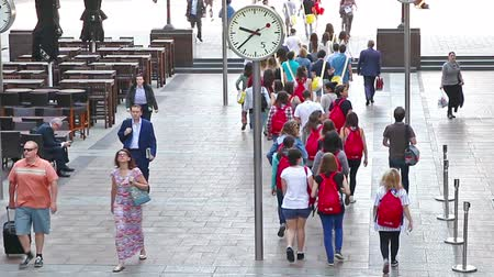 Лондон : LONDON, UK - JULY 03, 2015: Commuters, group of young people and tourists crossing Canary Wharf square.
