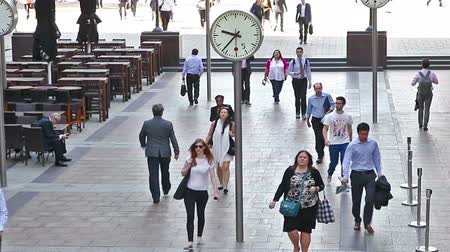 kerület : LONDON, UK - JULY 03, 2015: Group of young people, tourists and office people crossing the Canary Wharf square in morning hours