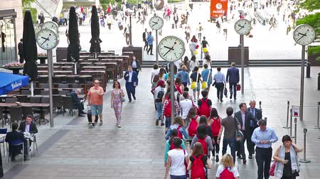 LONDON, UK - JULY 03, 2015: Group of young people, tourists and office people crossing the Canary Wharf square in morning hours