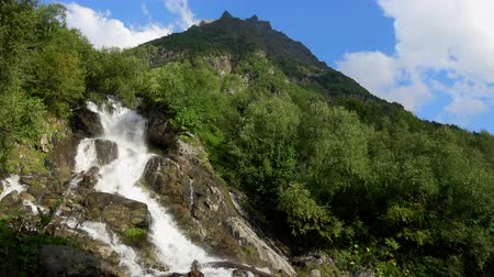 íngreme : View waterfall scenes in mountains, national park Dombai, Caucasus, Russia. Summer landscape, sunshine weather and sunny day Stock Footage