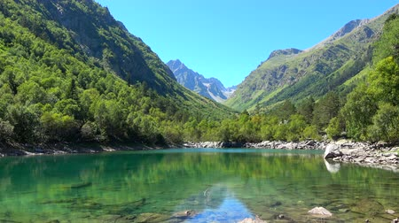 ravina : View lake scenes in mountains, national park Dombai, Caucasus, Russia, Europe. Summer landscape, sunshine weather, blue sky and sunny day Stock Footage
