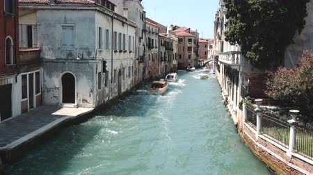 renaissance : Venice, Italy - July 1, 2018: Panoramic view of Venice narrow canal with historical buildings and boats traffic from Bridge Foscari. Landscape of summer sunny day and blue sky Stock Footage