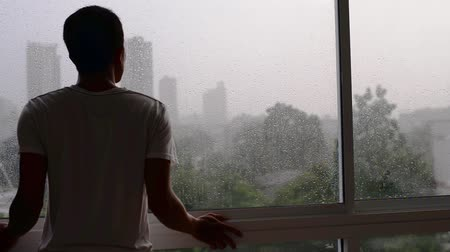 Lonely man waiting a rain and looking outside. Vídeos