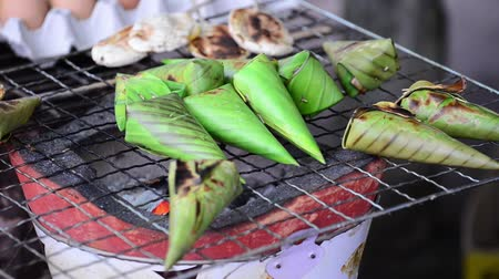 Sticky rice wrapped with banana leaf grilling on stove. Vídeos