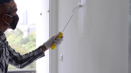 Painting white color on cement wall using paint roller. Vídeos