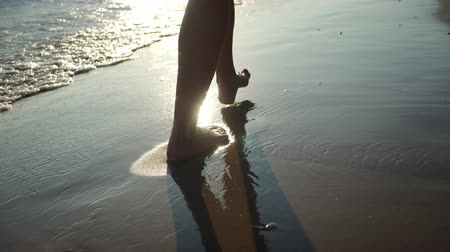 Young woman walking on beach in sea waves during sunset.
