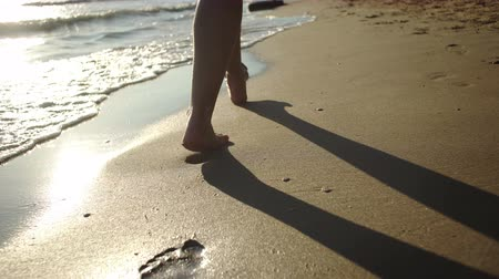 A young woman leaves footprints in the sand during the sunset.