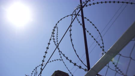 The sun shines through the barbed wire