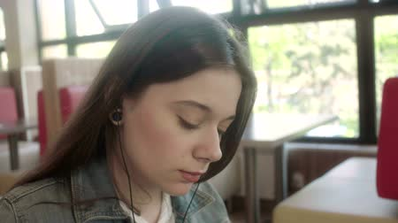 Young woman listening to music on headphones in a cafe Stock Footage