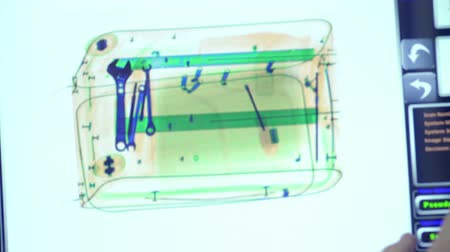 Baggage is scanned in x-ray scanner. Operator change the modes of the scanner.