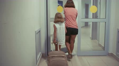 Young girl and her mother arriving at hotel, checking in, carrying luggage.