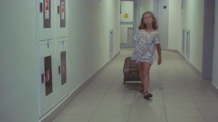 A little girl is rolling a suitcase down the hall in the hotel