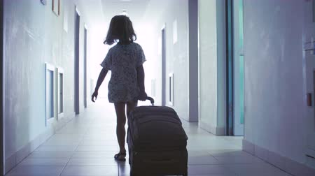 lobi : A little girl is rolling a suitcase down the hall in the hotel