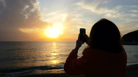 The girl is taking pictures of the sunset