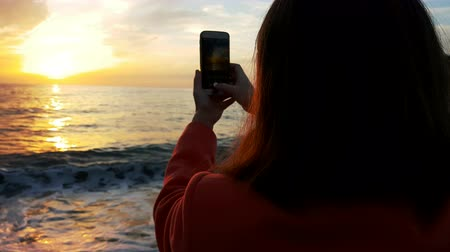 Alone girl watching sunset at sea, taking pictures.