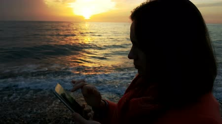 The girl is using her mobile at the sunset at the coast