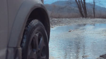 Splashes from under the wheels. Close up Slow motion. Country road.