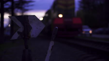The train stops at the railway arrow. Evening time, spotlight.