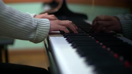 Hands of a young man play piano elegantly.