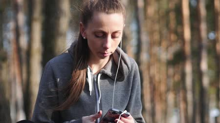 pléd : Young woman listen to music on her smartphone in the woods