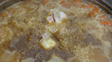 cop : Meat with rice, garlic and vegetables is cooked in a cauldron at the stake close up. Preparation of pilaf.